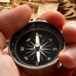 Hand holding compass on document folders background - Stock Photo