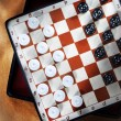 Stock Photo: Travelling draughts on playing field