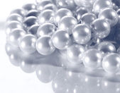 White pearl on reflective surface — Stock Photo