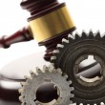 Steel cogwheels on judge's wooden gavel background — Stock Photo
