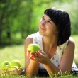Young woman with apples lying on grass — Stock Photo