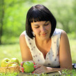 Young woman holding apple and reading book on grass — Stock Photo