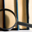 Stack of books and magnifying glass — Stock Photo #29296533
