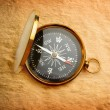 Stock Photo: Single golden compass on paper background