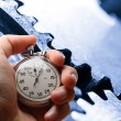 Stock Photo: Hand holding stopwatch and three steel cogwheels