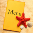 Stock Photo: Yellow menu book, seastar and seashells
