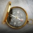 Stock Photo: Compass on steel scratchy background