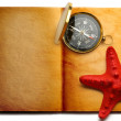 Stock Photo: Compass and red seastar on open book
