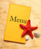 Yellow menu book, seastar and seashells — Stock Photo