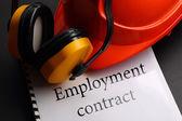 Employment contract with earphones and helmet — Stock Photo