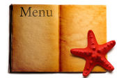 Open menu book and red seastar — Stock Photo