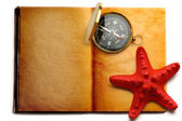 Compass and red seastar on open book — Stock Photo