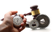 Steel cogwheels, wooden gavel and stopwatch in hand — Stok fotoğraf