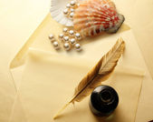 Envelope, feather and pearl — Stock Photo