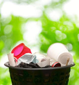 Wastebasket on green leaves — Stock Photo