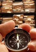 Hand with compass on paper documents — Stockfoto