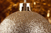 Golden bauble on a gold background. — Stok fotoğraf