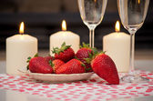 Champagne, strawberries and candles. — Stock Photo