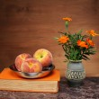 Peaches in a bowl, books and flowers — Stock Photo #34652085