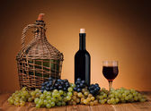 Woven wicker balloon wine and grapes — Stock Photo
