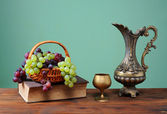 Grapes in a wicker basket and a metal carafe — Stock Photo