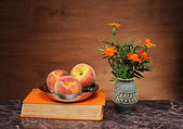 Peaches in a bowl, books and flowers — Stock Photo