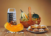 Decorative pumpkins in wicker baskets and pastries — Stock Photo