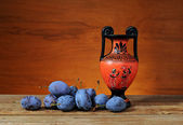 Fresh plums and amphorae — Stock Photo