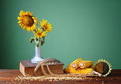Sunflowers in a ceramic vase and corn — Stock Photo