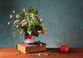 Flowers in a vase on a book and an apple — Foto de Stock