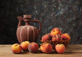 Fresh peaches and a ceramic pitcher — Stock Photo