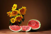 Sunflowers in a vase and watermelon — Stock Photo