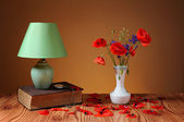Red poppy in a vase and table lamp — Stok fotoğraf