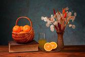 Sinaasappelen in rieten manden en bloemen — Stockfoto