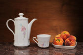 Dishes for tea and fresh peaches — Stockfoto