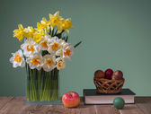 Daffodils in a vase of glass and easter eggs — Stock Photo