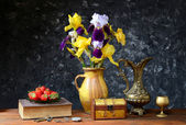 Irises in a ceramic vase and fresh strawberries — Stock Photo