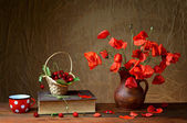 Red poppies in a ceramic vase, books,cherries and metal pots — Stock Photo