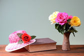 Roses in a ceramic vase, a book and a hat — 图库照片
