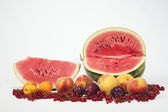Watermelon, peaches, plums and red currant — Stock Photo