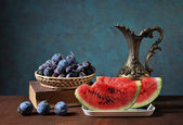 Watermelon slices and plums in wickerbasket — Stock Photo