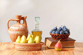 Ceramic carafe and fruits in a basket — Stock Photo