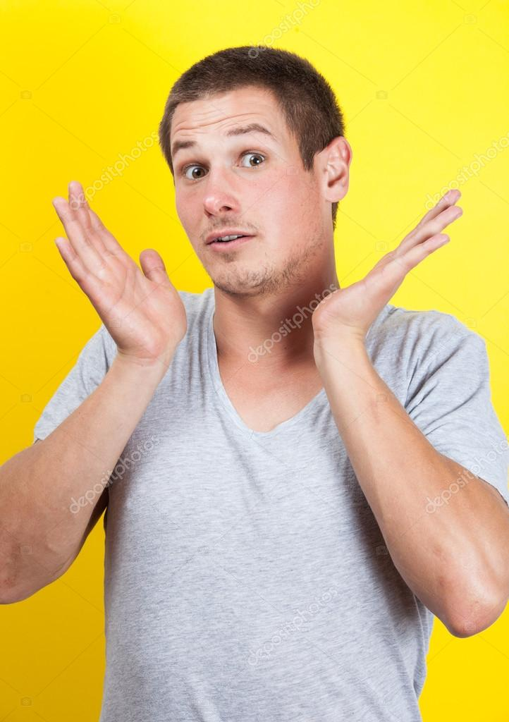 Surprised young man with hands in air, on yellow background  Stock Photo #16020097