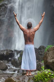 Handsome man at waterfall — Stock Photo