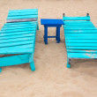 Two empty turquoise sunbeds at sandy beach. — Stock Photo