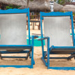 Two empty blue deckchairs at sandy beach. — Stock Photo