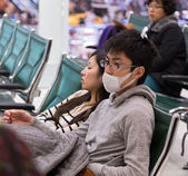 Young Asian man wearing protective mask in the waiting area of Doha International Airport — Stock Photo