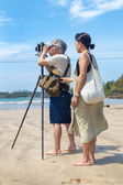 Japanese tourists stand on sandy beach and taking photos with old film camera — Stock Photo
