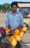 Local man selling fresh coconuts — Stockfoto