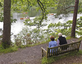 An Elderly Couple Watch Rowboats in a Lake — Stock Photo